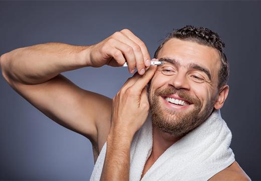 мужчина выщипывает брови