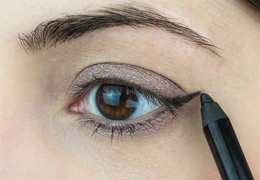 девушка красит глаз